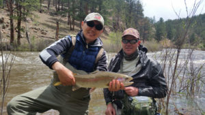 A angler holdiing a large rainbow trout, with his fly fishing guide Chris Galvin.
