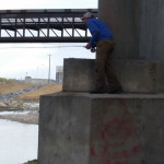Fly angler standing on bridge piling waiting to cast to unsuspecting carp.