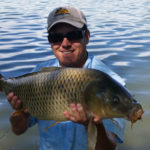 Flycarpin holding a sizable carp in partial shade with smooth water in background.