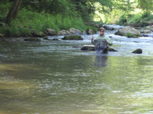 Chris Galvin running through river with trout in net