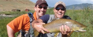 Two smiling friends kneeling along the Dream Stream in Colorado, one is holding a large brown trout.