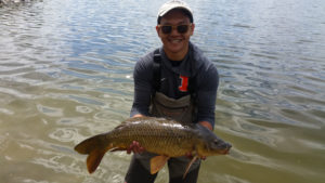 Young angler proudly holding a big carp with lake behind him