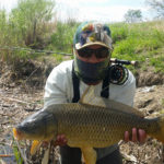 Angler in sunmask and fly rod over shoulder holding a large common carp
