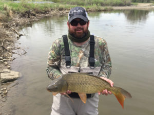 A happy fly fisherman with a big carp he caught in a Denver lake.
