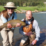 Female teen fly fisherman poses with guide, Chris Galvin, with a large cutbow trout.