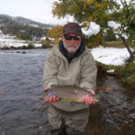 A pretty rainbow trout held above the river with a coating of early snow in the background.