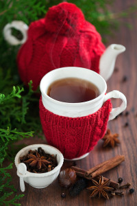 tea pot and tea cup with hot black tea wrapped in red knitted cover