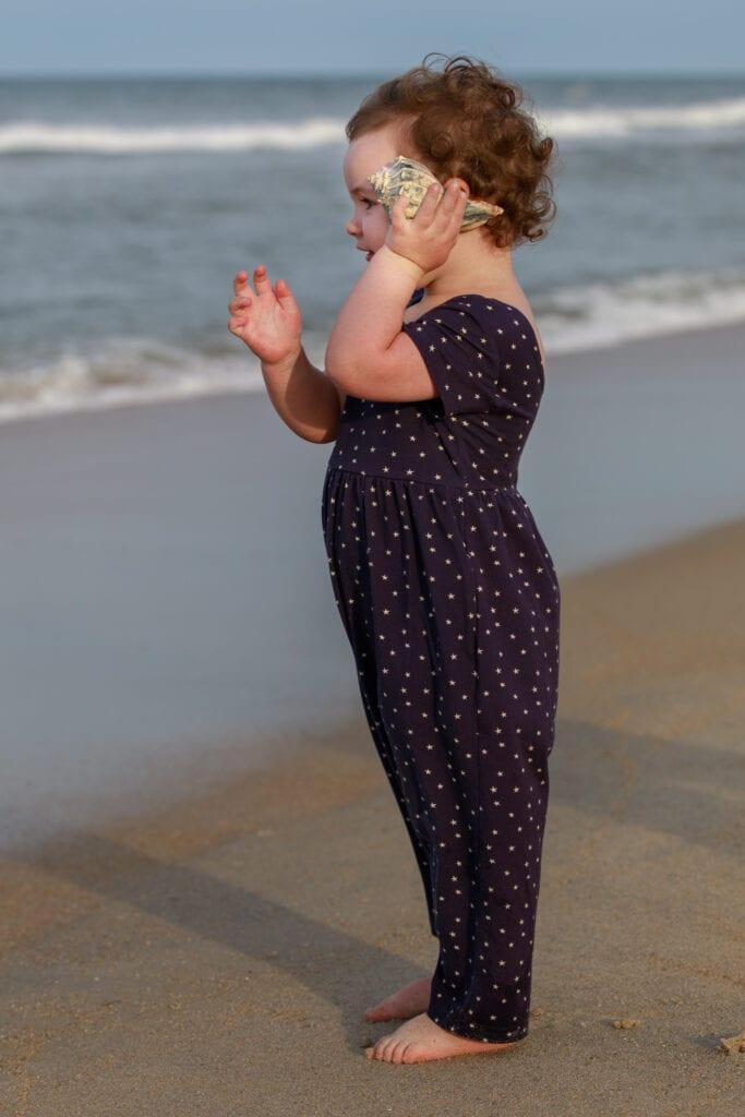 Little girl holding sea shell to hear the ocean Duck NC