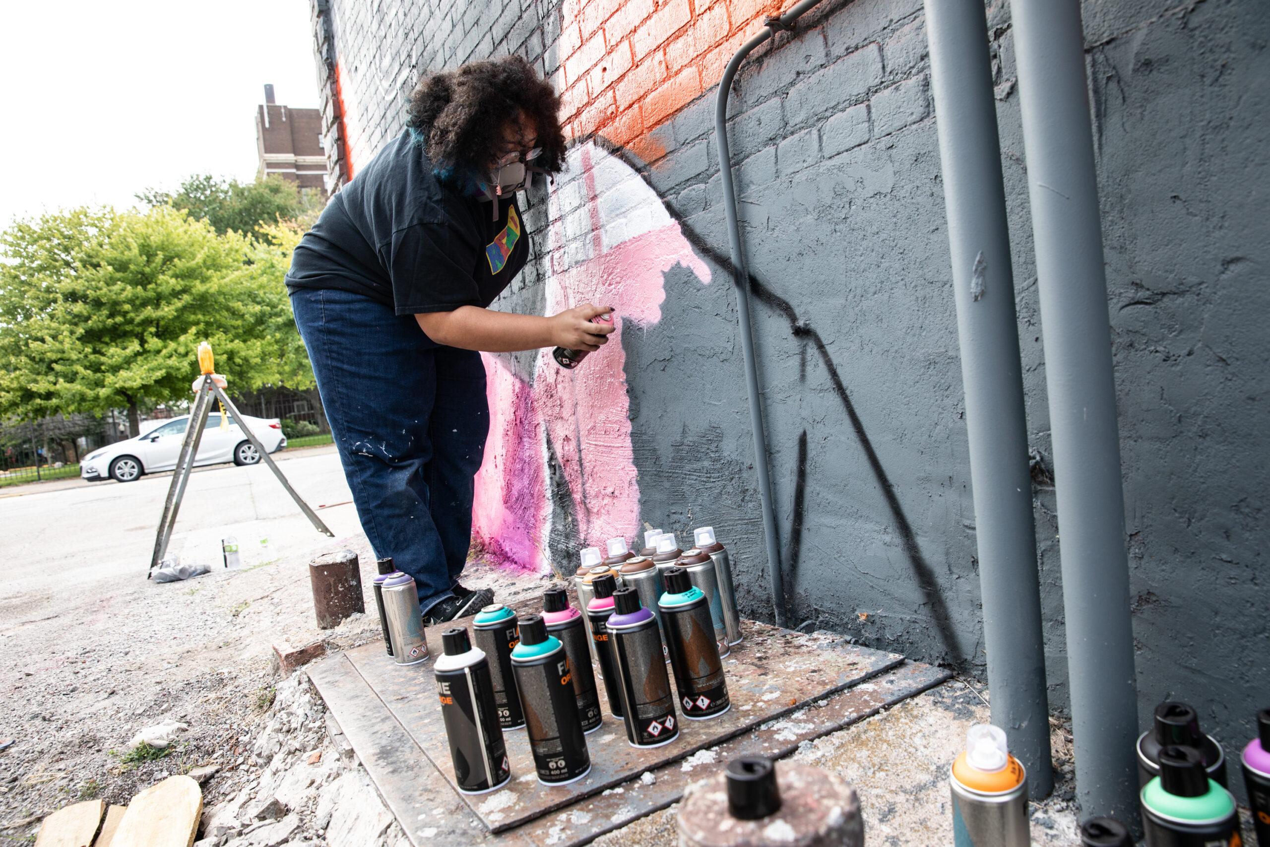 Rock Island High School Student Riley Jones working on the mural