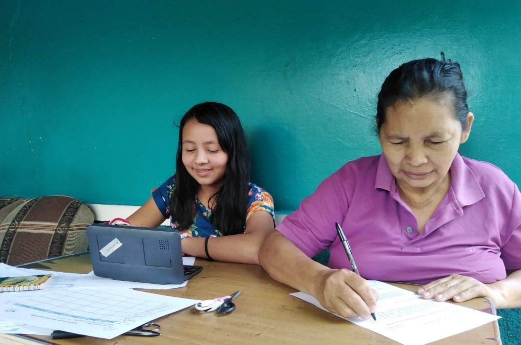 Laura, a 7th grader, and her grandmother picking up a tablet so she can study from home.