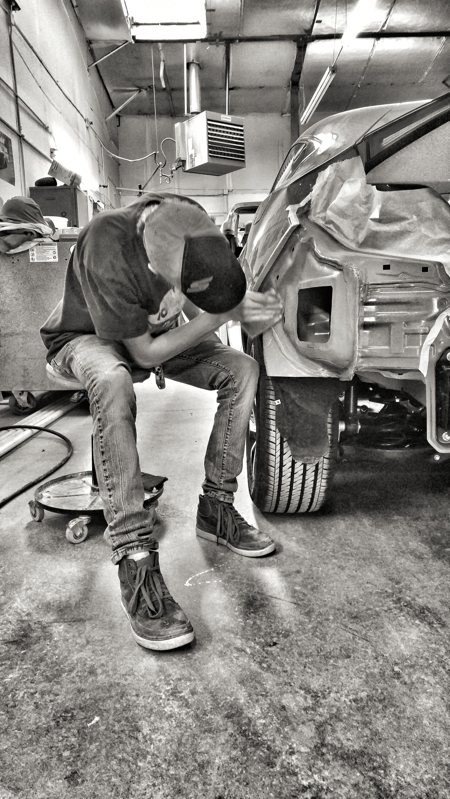 Gentleman is sanding a car for auto body repairs.