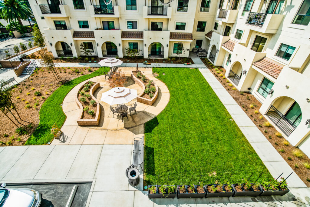 A view from the balcony looking at the courtyard, private outdoor seating area, and benches at Gladstone Senior Villas.