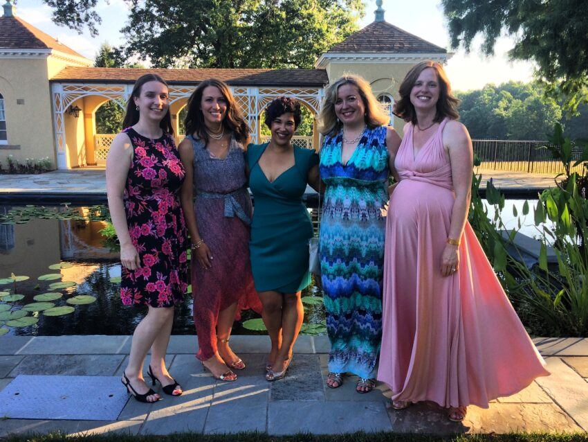 Five women standing together, dressed up for an event, with Felicia in the center