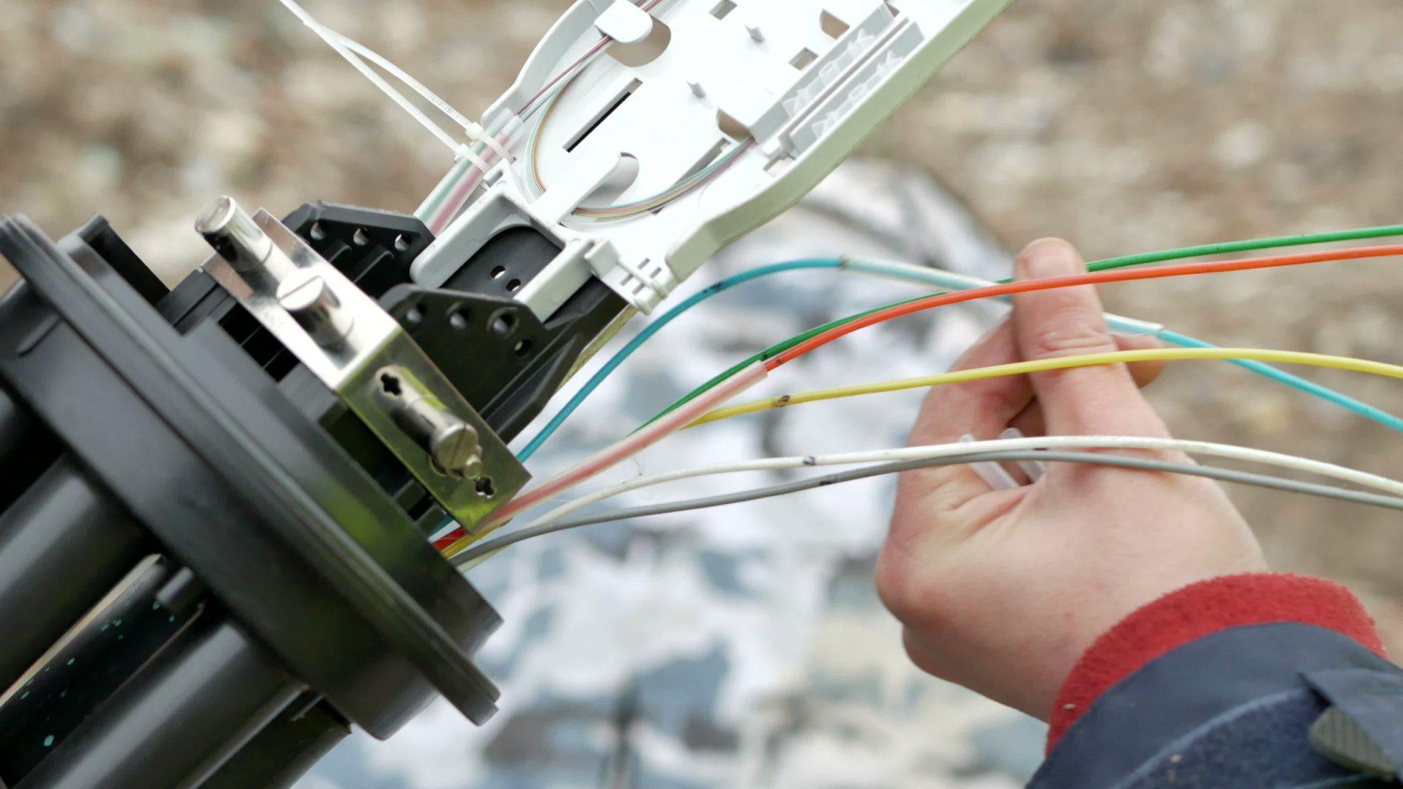 Man installing fiber optic cable into a conduit