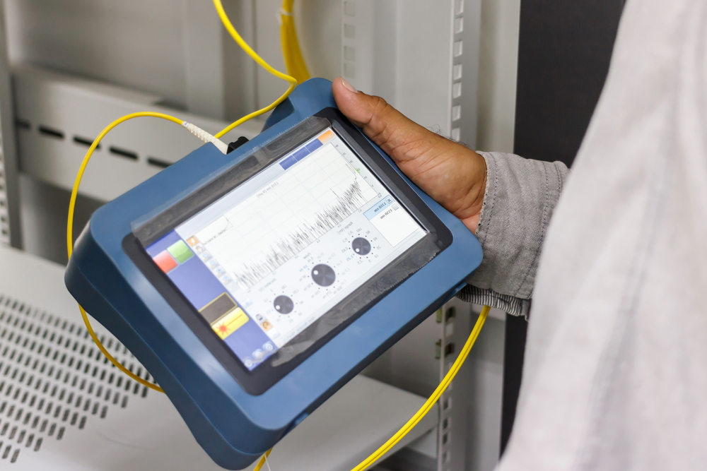 Man holding a fiber optic cable testing device