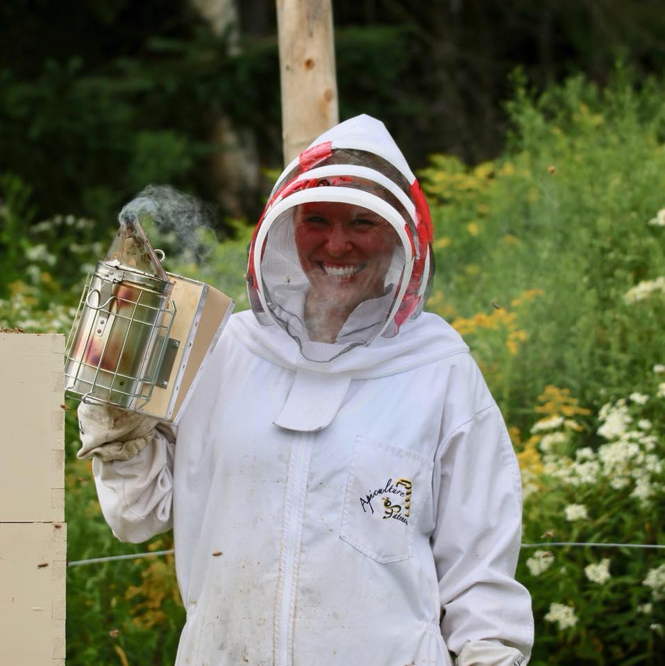 Sophie Roy dehors en tenue d'apicultrice.