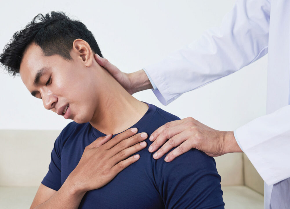 Young Vietnamese man complaining about pain in his neck