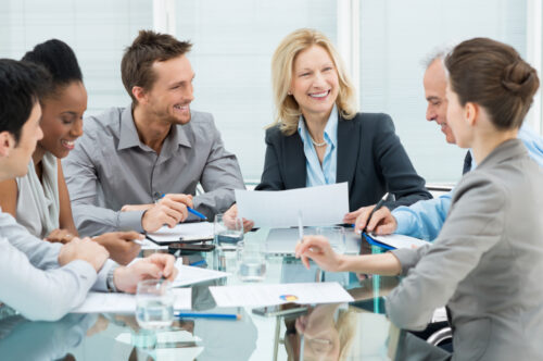 Picture of business people sitting around a glass desktop signing papers