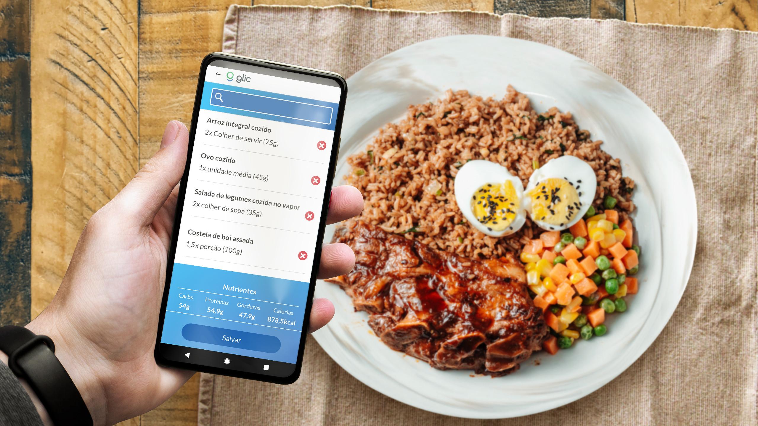 Uma pessoa segura um celular na mão com a tela do Glic app aberta indicando os alimentos que está ingerindo, ao fundo um prato de comida sobre uma mesa de madeira com arroz, ovos, legumes e costela de boi