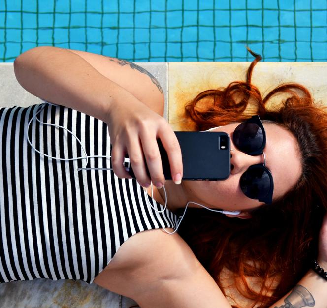 Uma mulher utilizando o celular deitada perto de uma piscina.