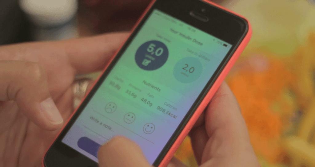 Mãos femininas seguram um celular laranja, a tela mostra o uso do App da Glic
