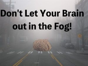 Picture of a foggy day in a city with a brain on a street that's in the fog.
