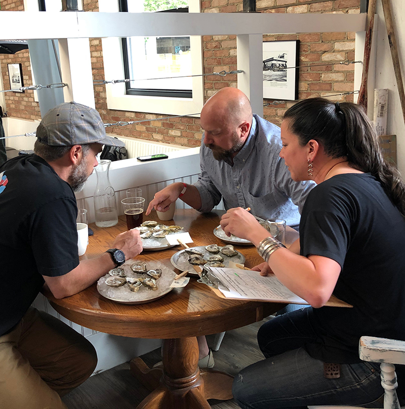 The judges of the Alberta Oyster Fest oyster shucking competition deliberate.