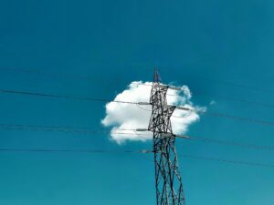 Utility lines in front of a blue sky with a cloud