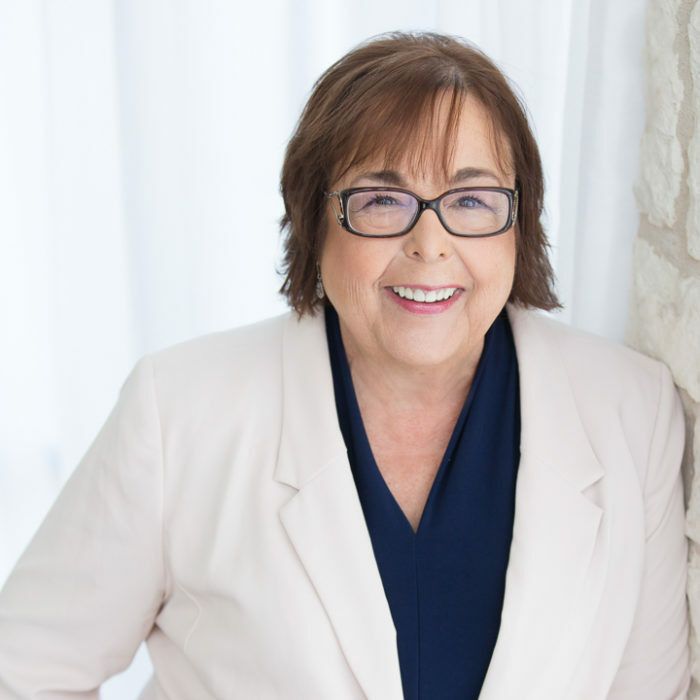 A portrait of Patti Rossman, co-founder of the Life Science Women's Network, Life Science Women's Conference and President of Globiox. She has a bright smile, is wearing a white suit, black rectangular glasses, and has short brown hair.