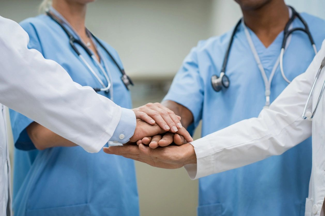 A group of medical professionals bringing their hands together in team salute.