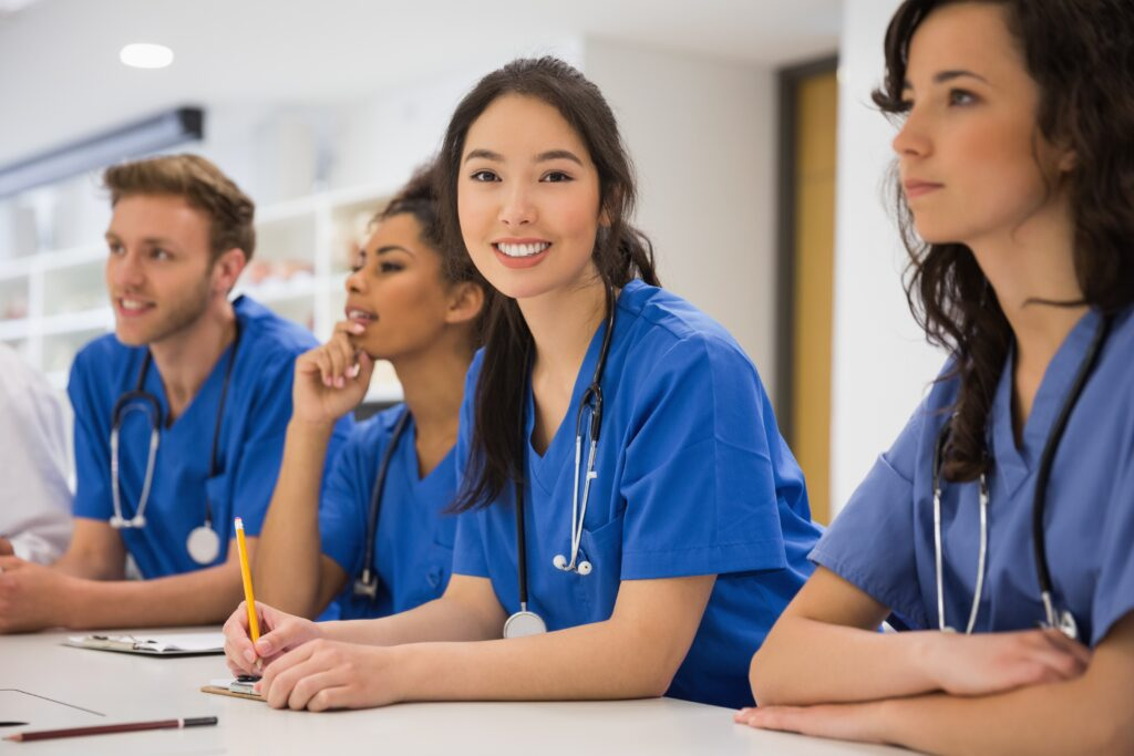 A photo of medical students. The focus is a woman smiling at the camera with long black hair in an over-the-shoulder ponytail. They're all in blue shirts.  Student memberships would be perfect for them.