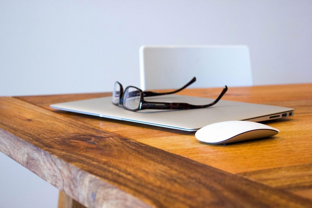 Re-opening the workplace header. Features glasses on a laptop next to a mouse on a wooden table.