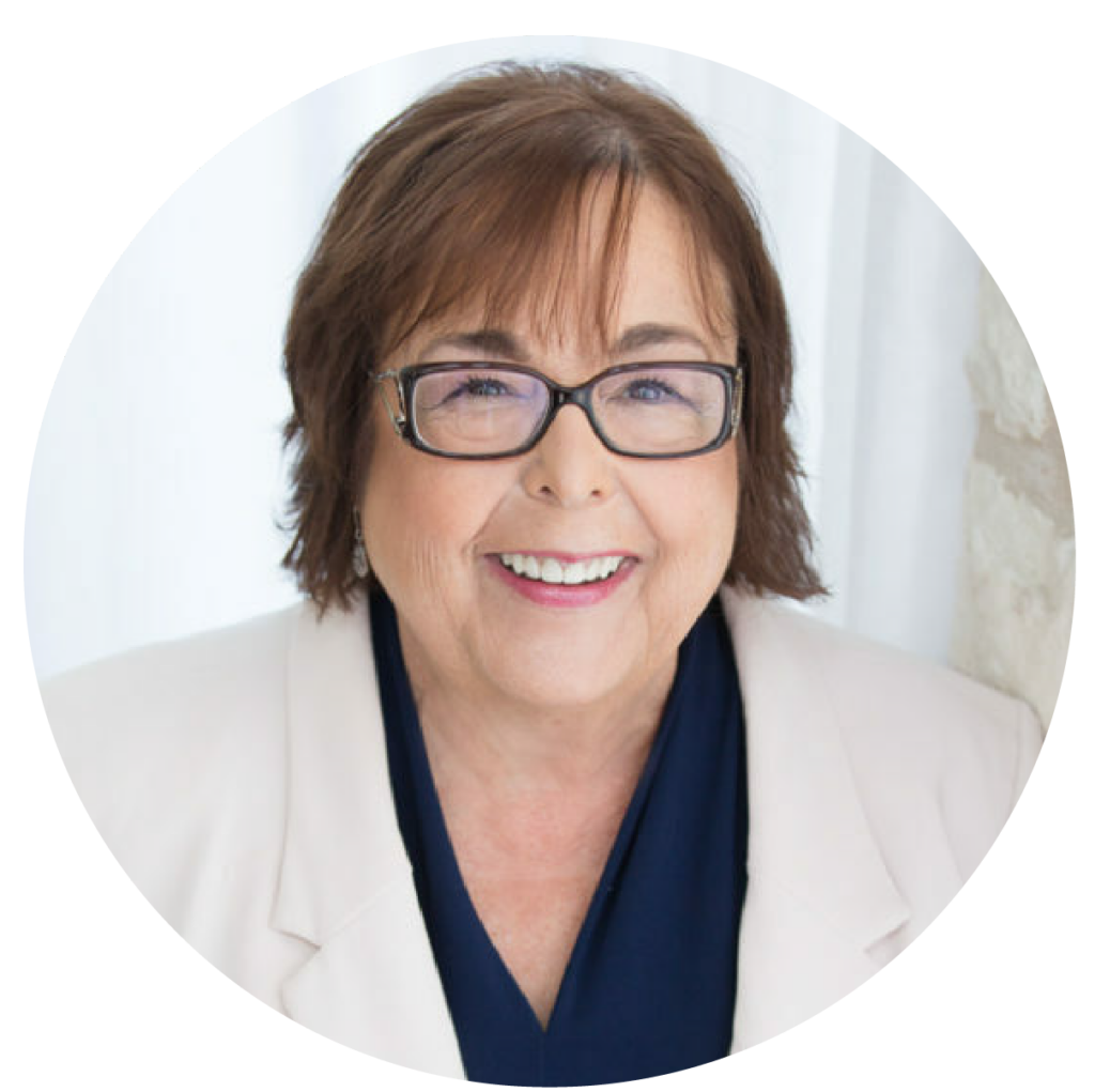 Patti Rossman, a speaker and co-founder. She has chin-length brown hair, rectangular black glasses, and a bright smile.