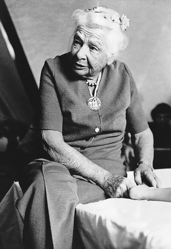 Black and white image of Dr. Ida Rolf with her hands on a client's foot