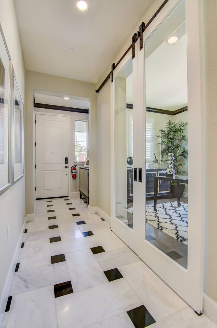 hallway with biparting white sliding doors mounted with black barn door hardware
