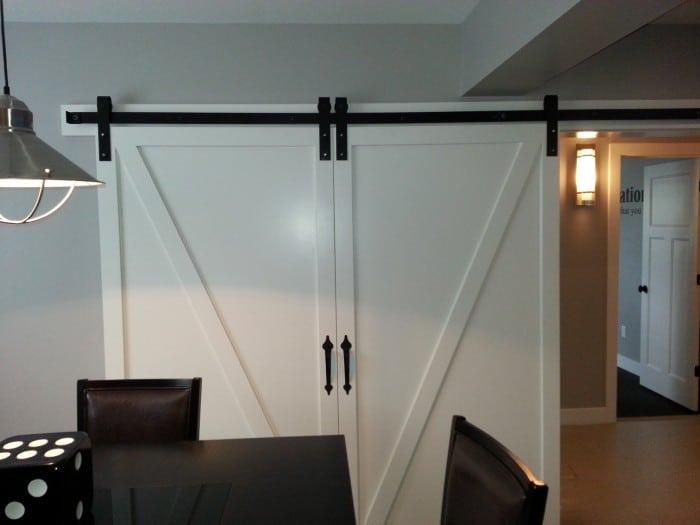 white bipartind sliding doors with black barn door hardware