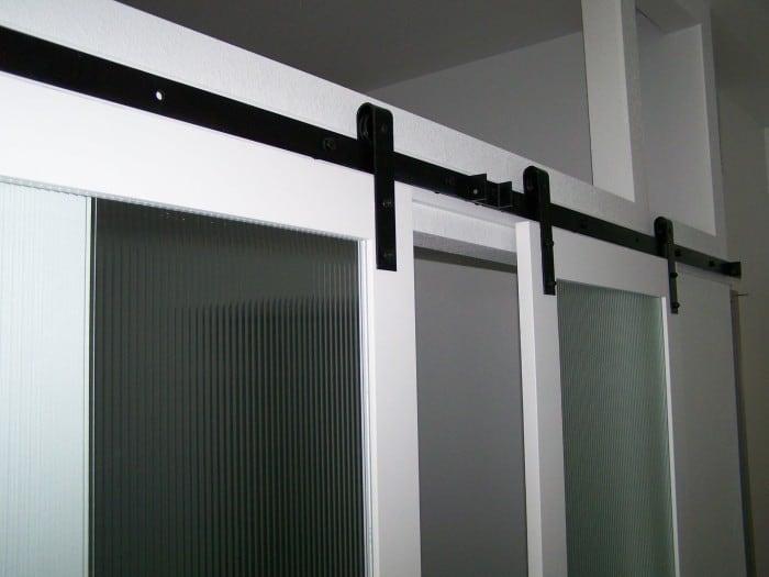 white biparting sliding doors with black barn door hardware