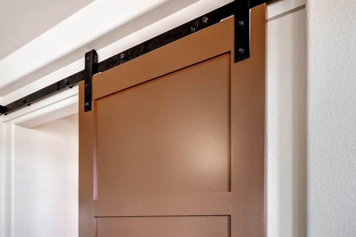brown sliding bathroom door with black barn door hardware