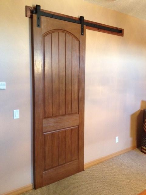 Decorative wood sliding door with black barn door hardware