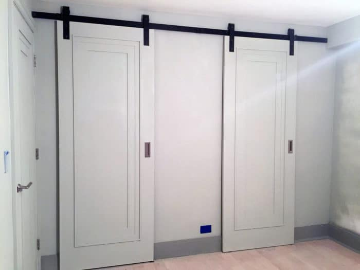 two white sliding closet doors with black barn door hardware