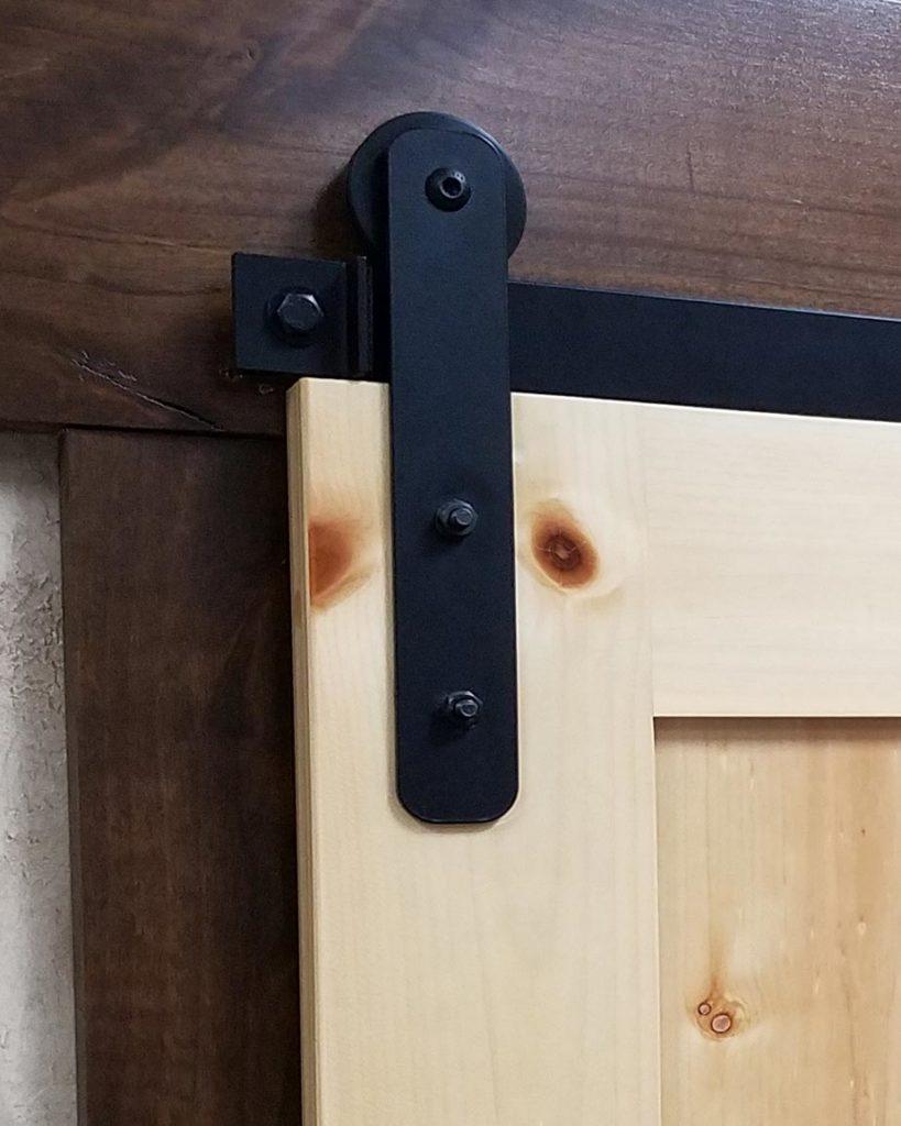 pine door with black light-duty barn door hardware and track