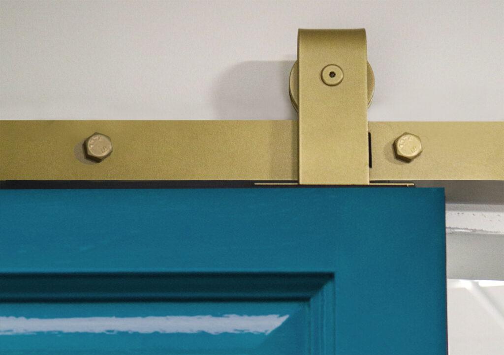 Blue door with Goldberg Brothers top mount barn door hardware in Jacob's Gold finish