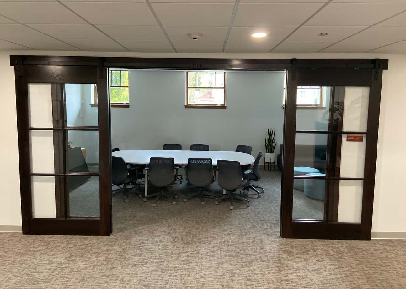 Goldberg Brothers barn door hardware on a pair of biparting conference room doors