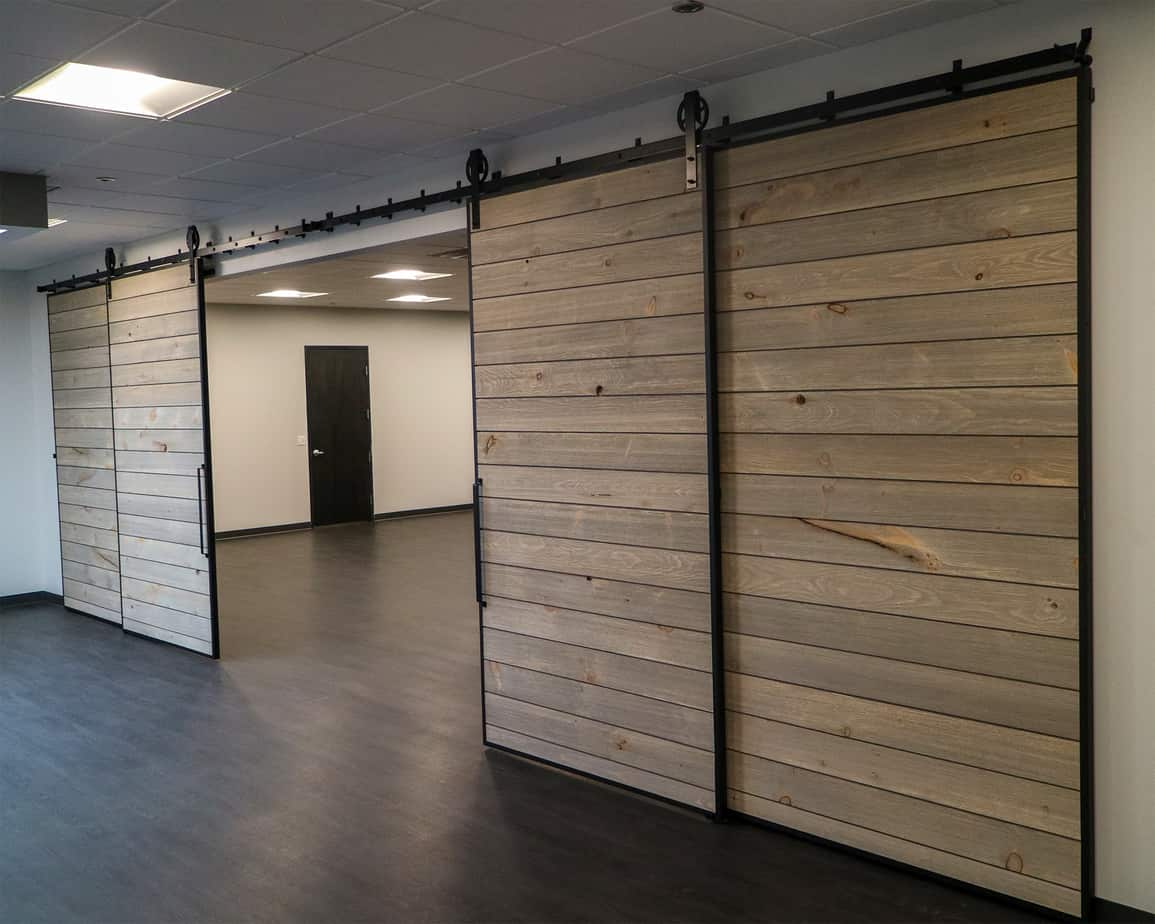 four large, shiplap slat doors with black steel edge channels