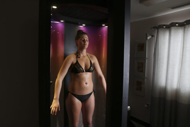 Woman Spray Tanning in Norvell Auto Revolution at Tanning Cabana