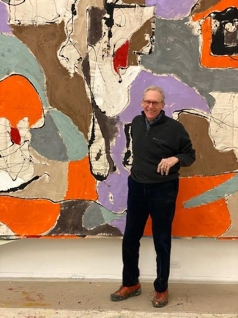 Tom Goldenberg standing in front of painting