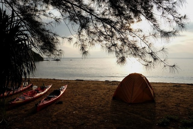 tent and boats on beach at dawn
