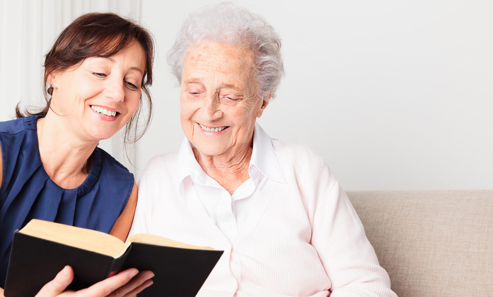 Photo of a woman reading a book with an elderly woman