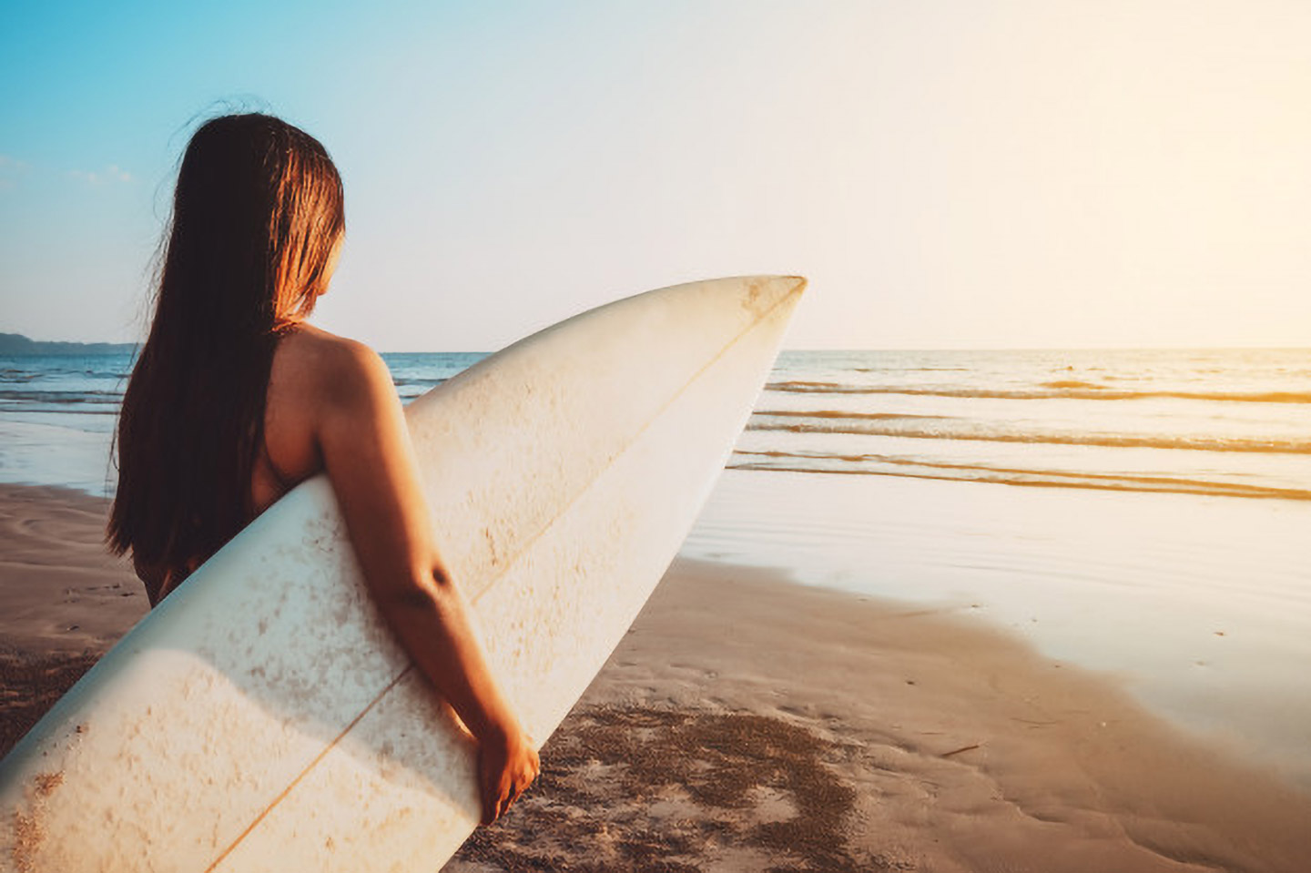 Image of a teen staring at the ocean holding a surfboard