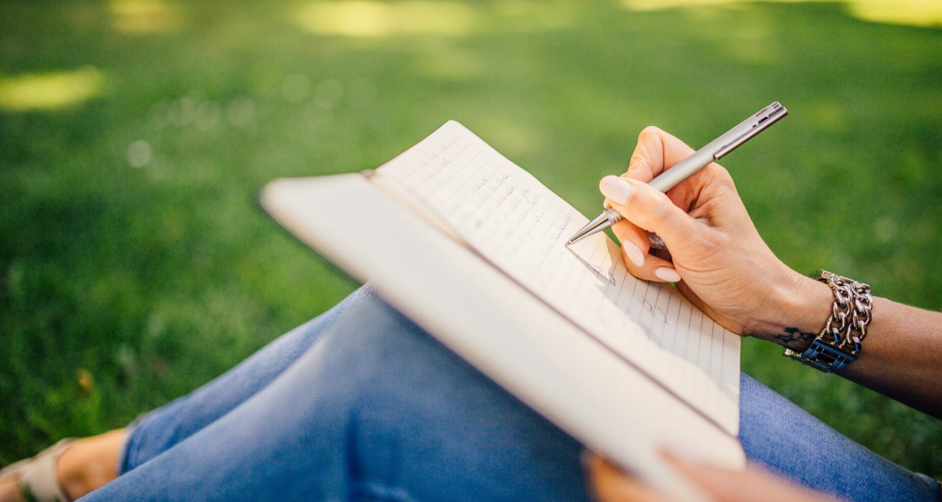 Photo of a woman writing on a Notebook